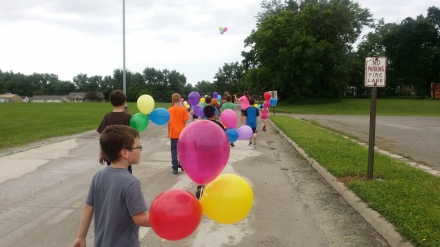 The kids in my summer program walking to the back of the field to release their balloons (it has a postcard attached to each one that's pre-addressed with a stamp).